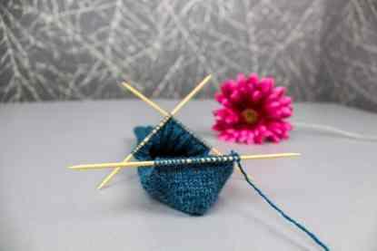 Gestrickte Herzchenferse für Socken auf einem Nadelspiel