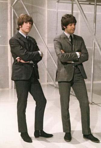 John y Paul, ambos con la misma postura y cargando el peso sobre su pierna izquierda.