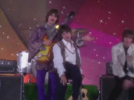 George pasando la mano por encima de su hombro para señalar a John.