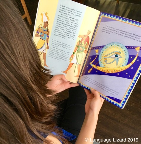 Child reads bilingual book about Egyptian mythology