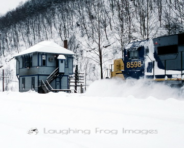 An eastbound freight train kicks up the snow as it passes HO Tower in Hancock, WV after the Blizzard of 1996.
