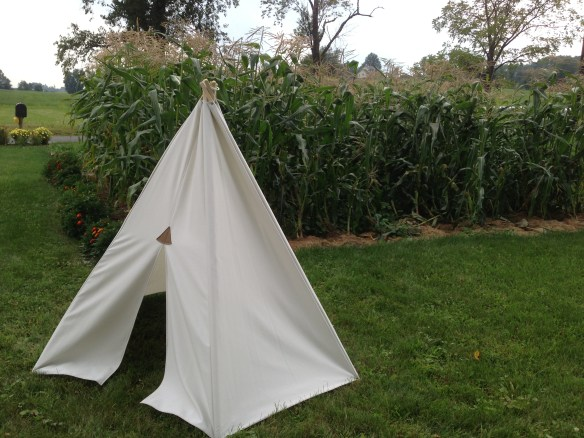 Fresh from the sewing machine, this Child's Teepee tent stands next to Sarah's sweet corn bed.