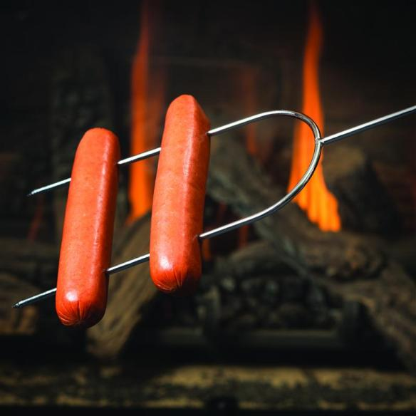 Hot dog roasting fork in front of fire