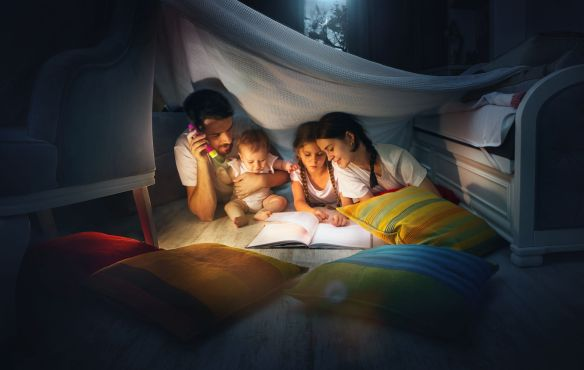 Family with flashlight reading