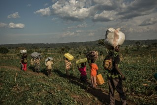 KYANGWALI REFUGEE CAMP, UGANDA - MARCH 23: Congolese refugees carry their belongings after being assigned space in the Kyangwali refugee resettlement camp in Uganda on March 23, 2018. Violence in Ituri Province in northeastern Democratic Republic of Congo has displaced more than 400,000 people including approximately 40,000 refugees who have fled to Uganda. (Photo by Andrew Renneisen for The Washington Post)