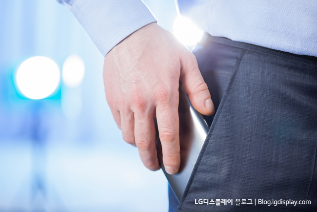 Businessman puts a smartphone in the pocket