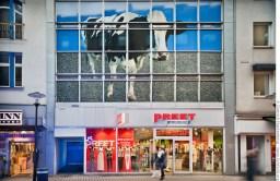 Kuh montiert von der Künstlerin Susanne Henning ziert das Gebäude über dem Modegeschäft Preet. Foto © Dietrich Hackenberg