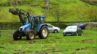 Cars being towed from the mire in the aftermath of the abandoned fell race