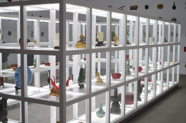 Brightly lit shelves housing Chinese artifacts