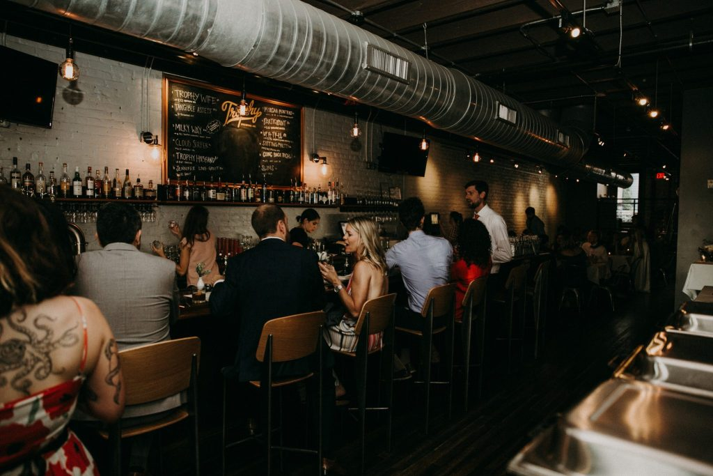 Wedding reception guests mingle at Tap & Table's bar and enjoy craft beer.
