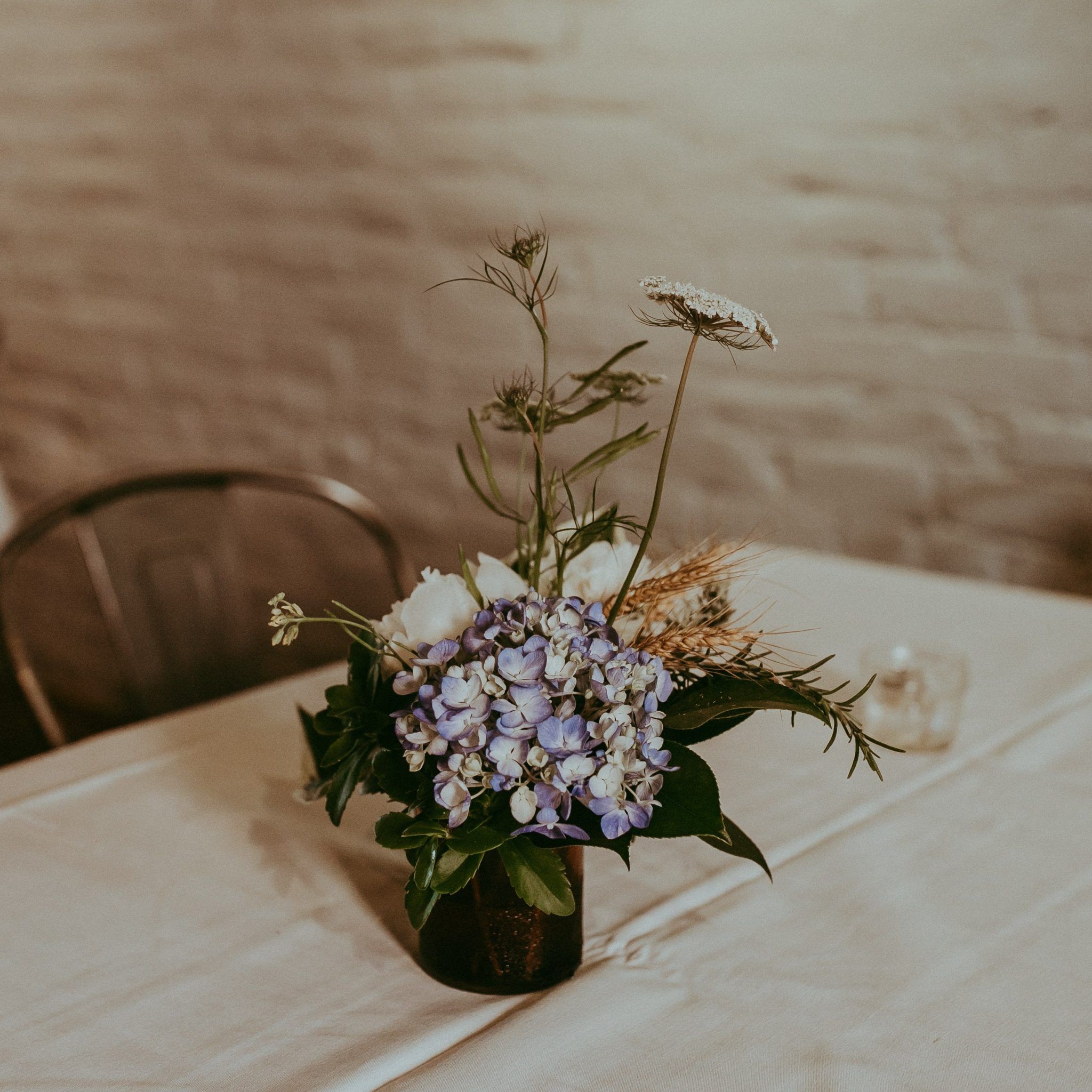 Asymmetrical wedding flower arrangement with blue hydrangea, wheat, and wild flowers in upcycled brown glass vase on white linen