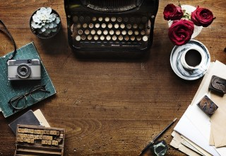 Stock image of a typewriter and publishing materials on a desk