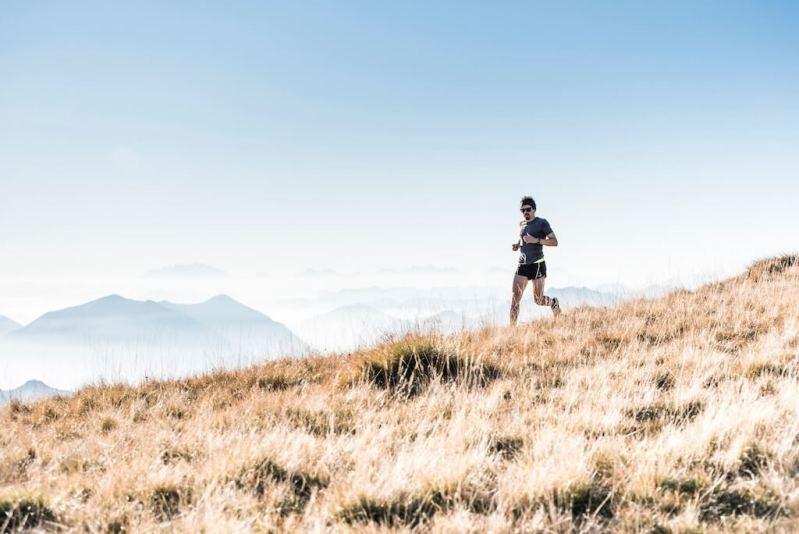 ein Mann, der auf einem Hügel in der Sonne joggt