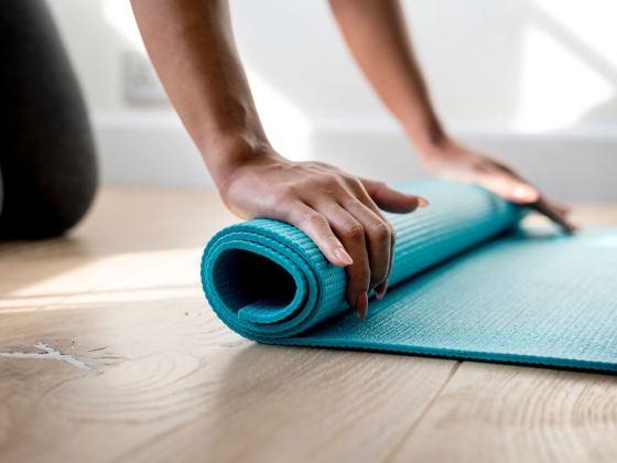 Die Yogamatte mit zwei Händen aufrollen