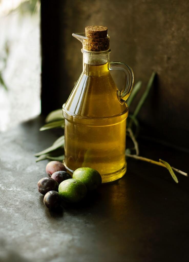 Linolöl in einer Flasche mit grünen Oliven