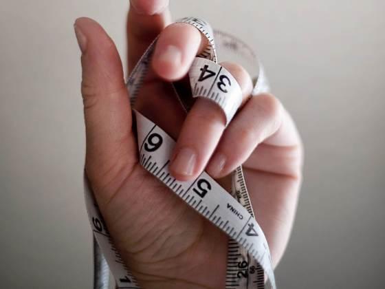 Hand, die ein Maßband hält, um Stoffwechsel bildlich darzustellen