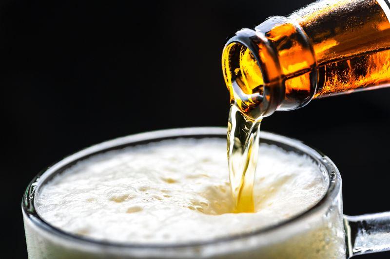 Bier aus der Flasche in ein fast volles Glas gießen