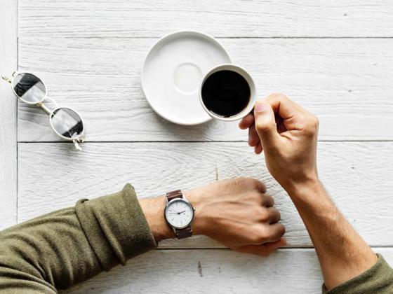 Arme einer Person, die eine Uhr trägt und einen Kaffee trinkt, was symbolisch für fasten stehen soll.
