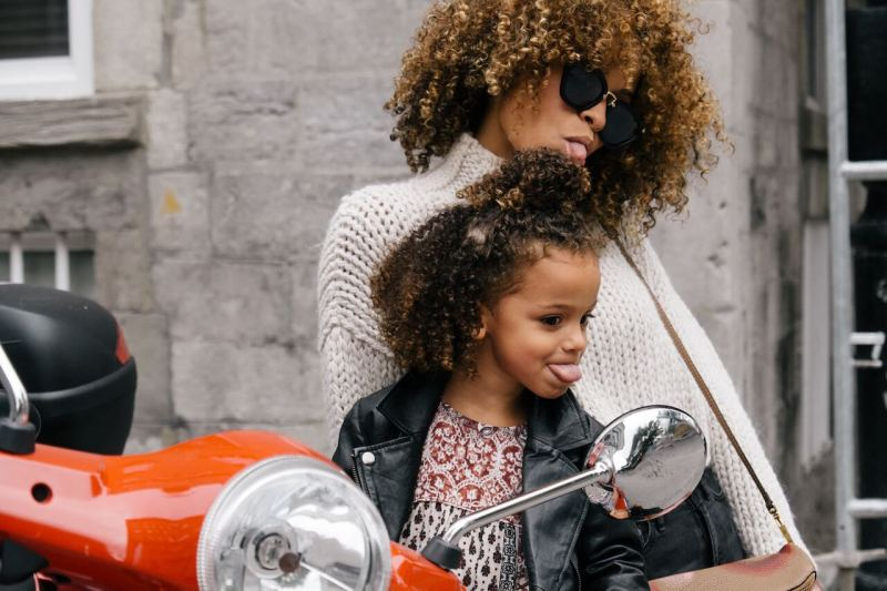 Mutter und Tochter betrachten sich im Motorrad-Rückspiegel