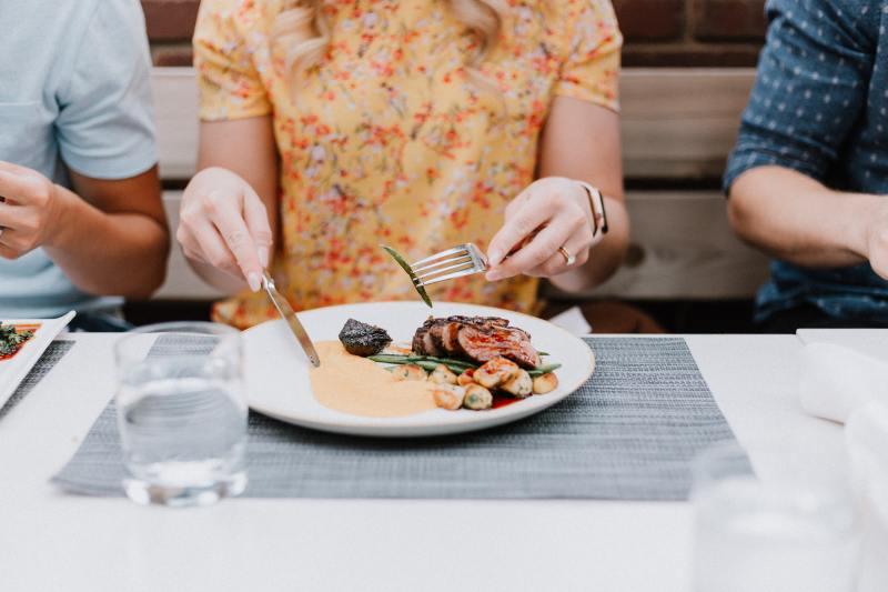 Frau die ein Teller mit Steak vor sich hat