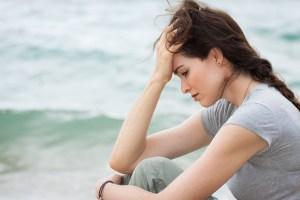 Jeune femme dépressive assisse sur la plage
