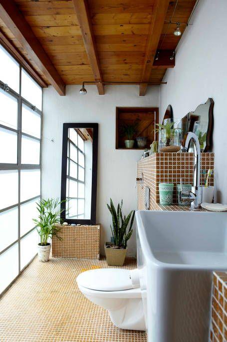 Une très belle salle de bain de style industriel, avec ses poutres apparentes en bois naturel et son carrelage cuivré. Découvrez les photos de ce loft sud africain dans l'article !