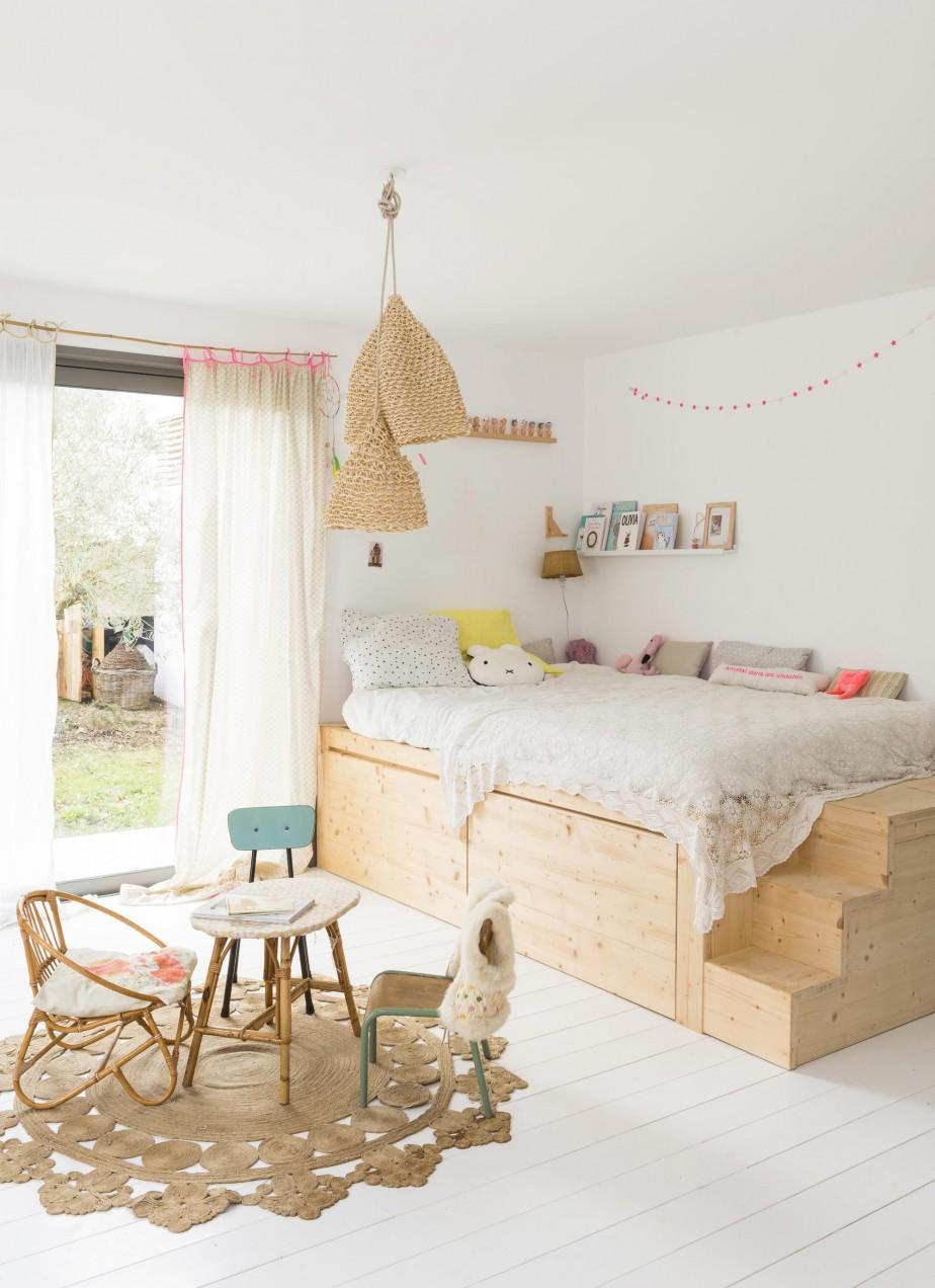 Une jolie chambre d'enfant, décorée de meubles en bois clair et de quelques touches de couleurs douces. Retrouvez toutes les photos de cette maison familiale dans l'article.