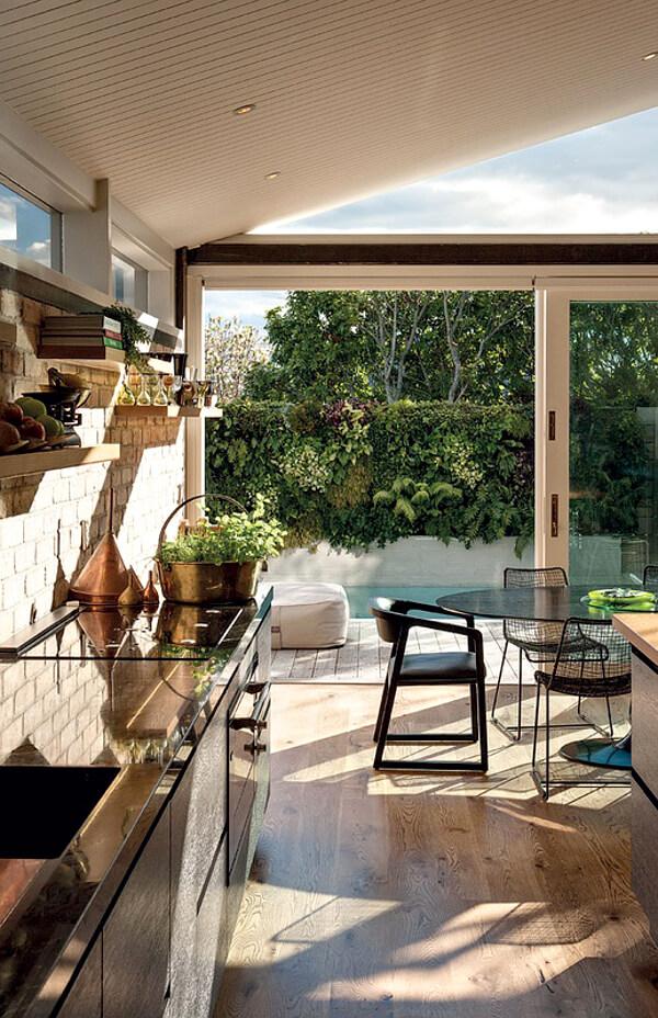 Un jolie salle à manger chic et design, avec son carrelage blanc et ses objets cuivrés. Retrouvez toutes les photos de ce cottage néo-zélandais dans l'article.
