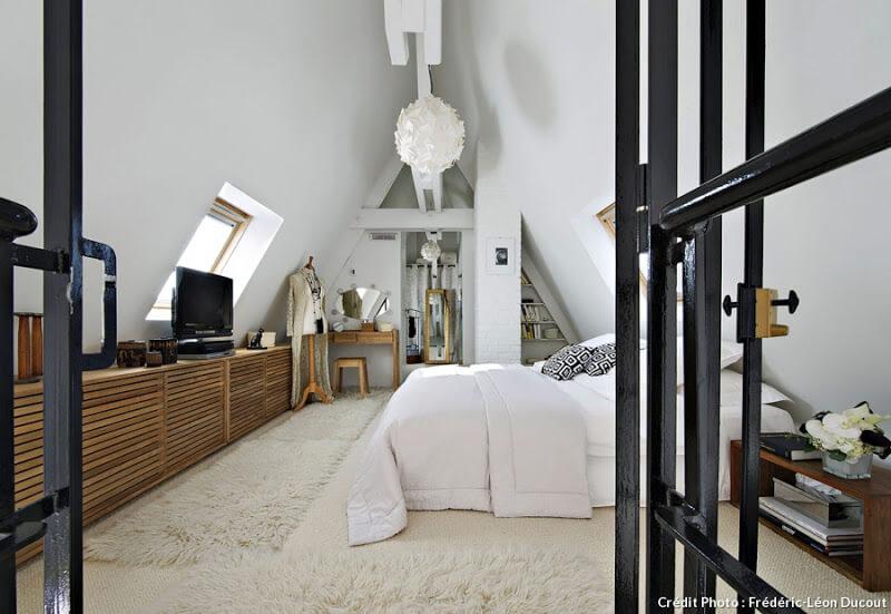 Une chambre à la décoration industrielle et cosy, avec des tapis tout doux et du bois naturel. Découvrez plus de photo de ce loft parisien dans l'article.
