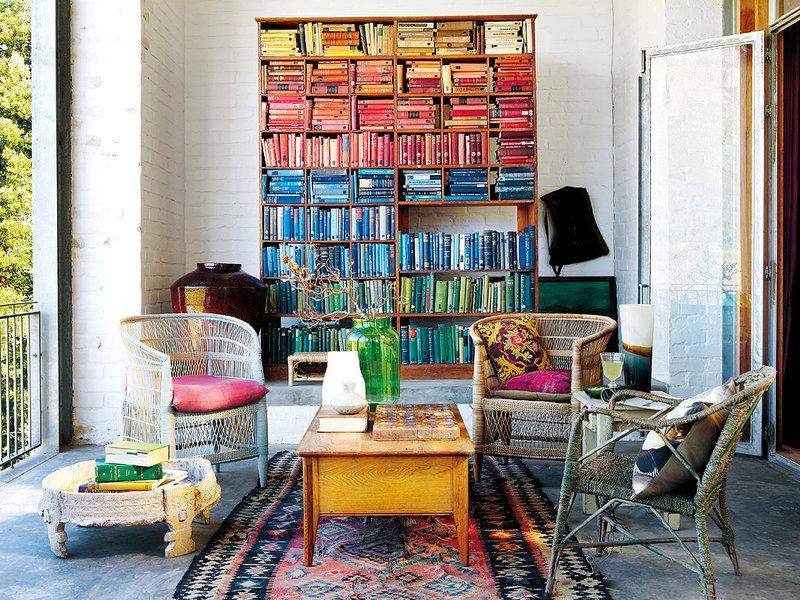 Quelle jolie leçon de style avec cette magnifique bibliothèque classée par couleur ! Découvrez les autres photos de ce salon bohème dans l'article.