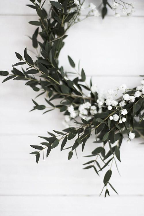 Une couronne de Noel réalisée avec de petites fleurs blanches
