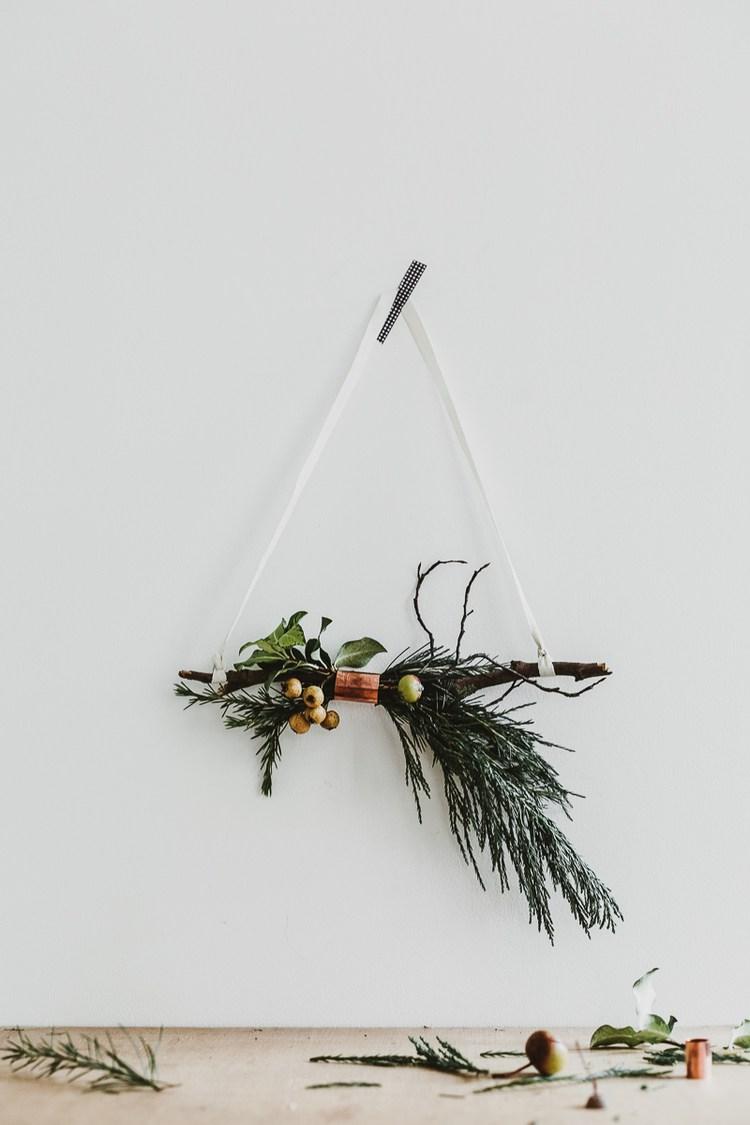 Une couronne de Noel originale, réalisée avec des branches de sapins et un anneau de cuivre