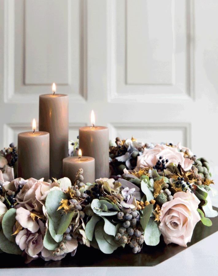 Un centre de table décoré avec des bougies et une couronne de noel