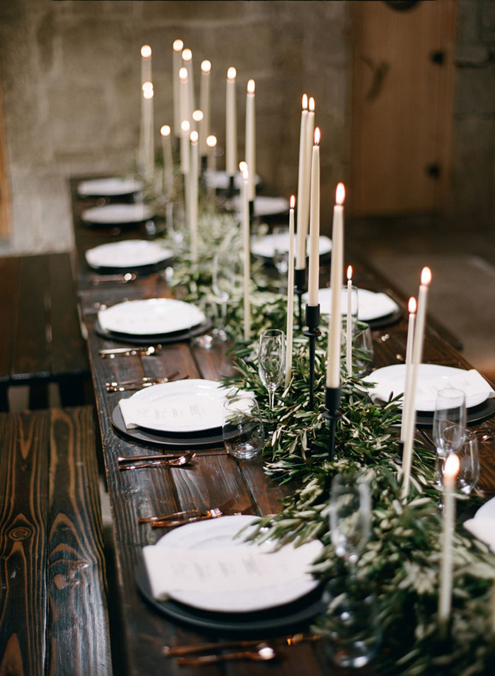 Une table de noel naturelle décorée de bougies et de grands chandeliers