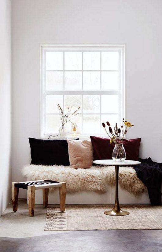 Un salon cosy avec une couverture en fausse fourrure et des coussins de velours