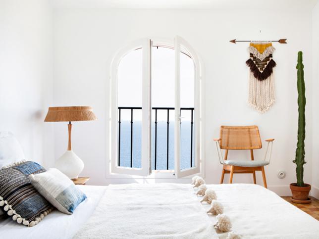Une déco bohème dans la chambre, avec un tissage mural et des coussins ethniques