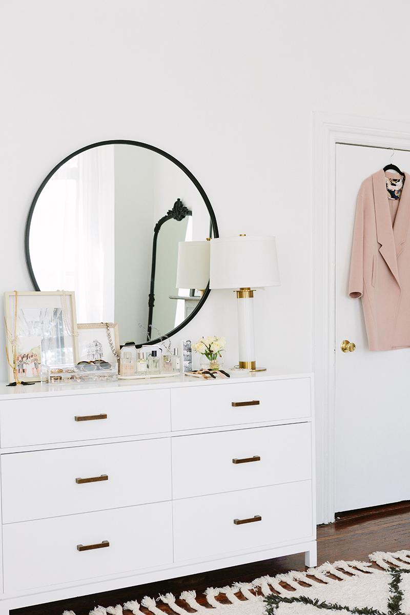 Une chambre à la déco féminine avec ce beau miroir rond sur la commode