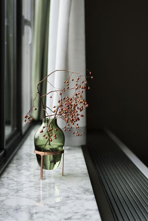 Des baies rouges dans un vase design en verre fumé