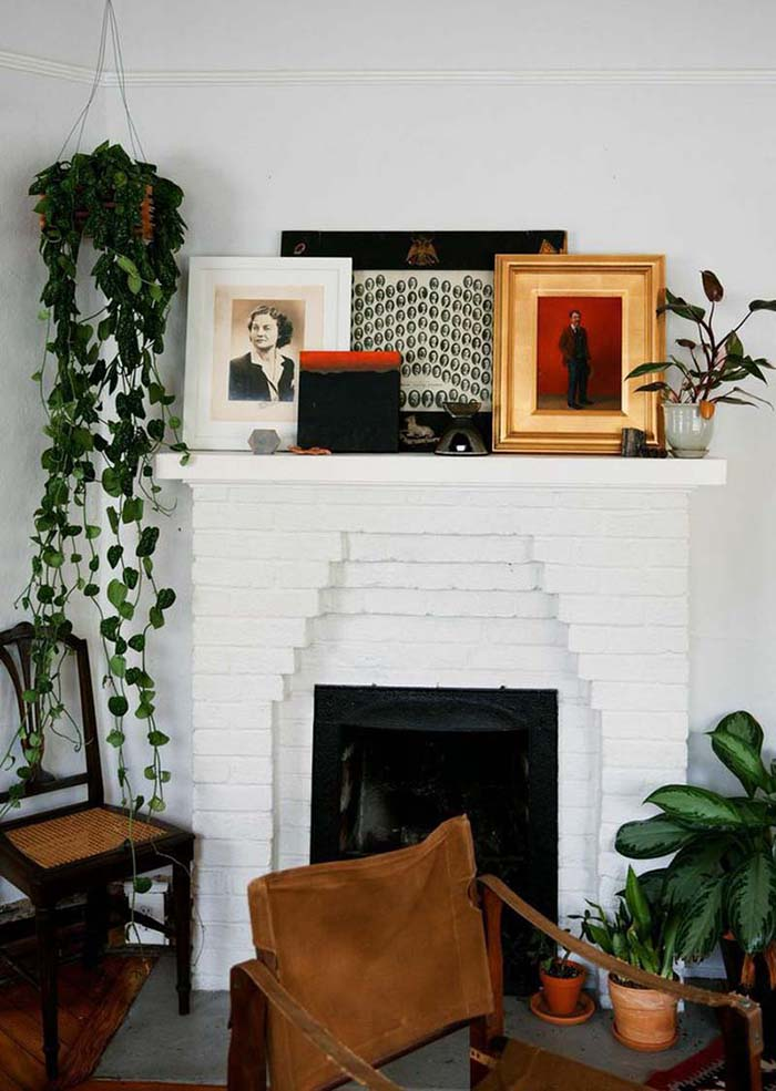 Une cheminée décorée avec une accumulation de tableaux