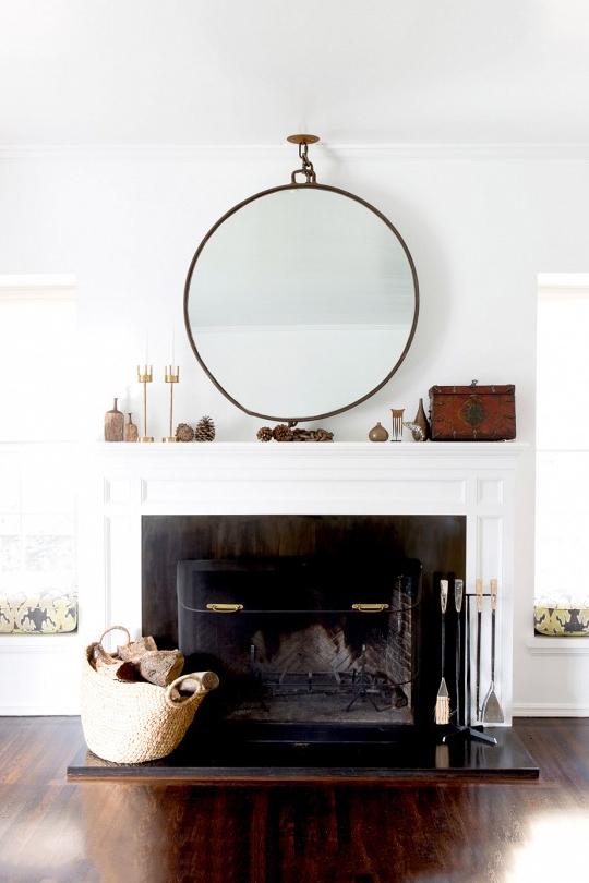 Un miroir rond au dessus d'une cheminée