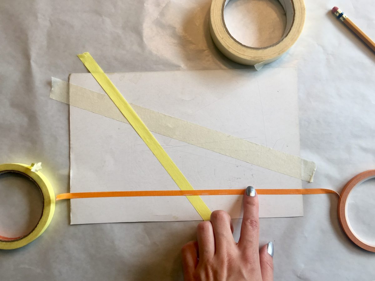 Three pieces of tape stretched across each other on paper