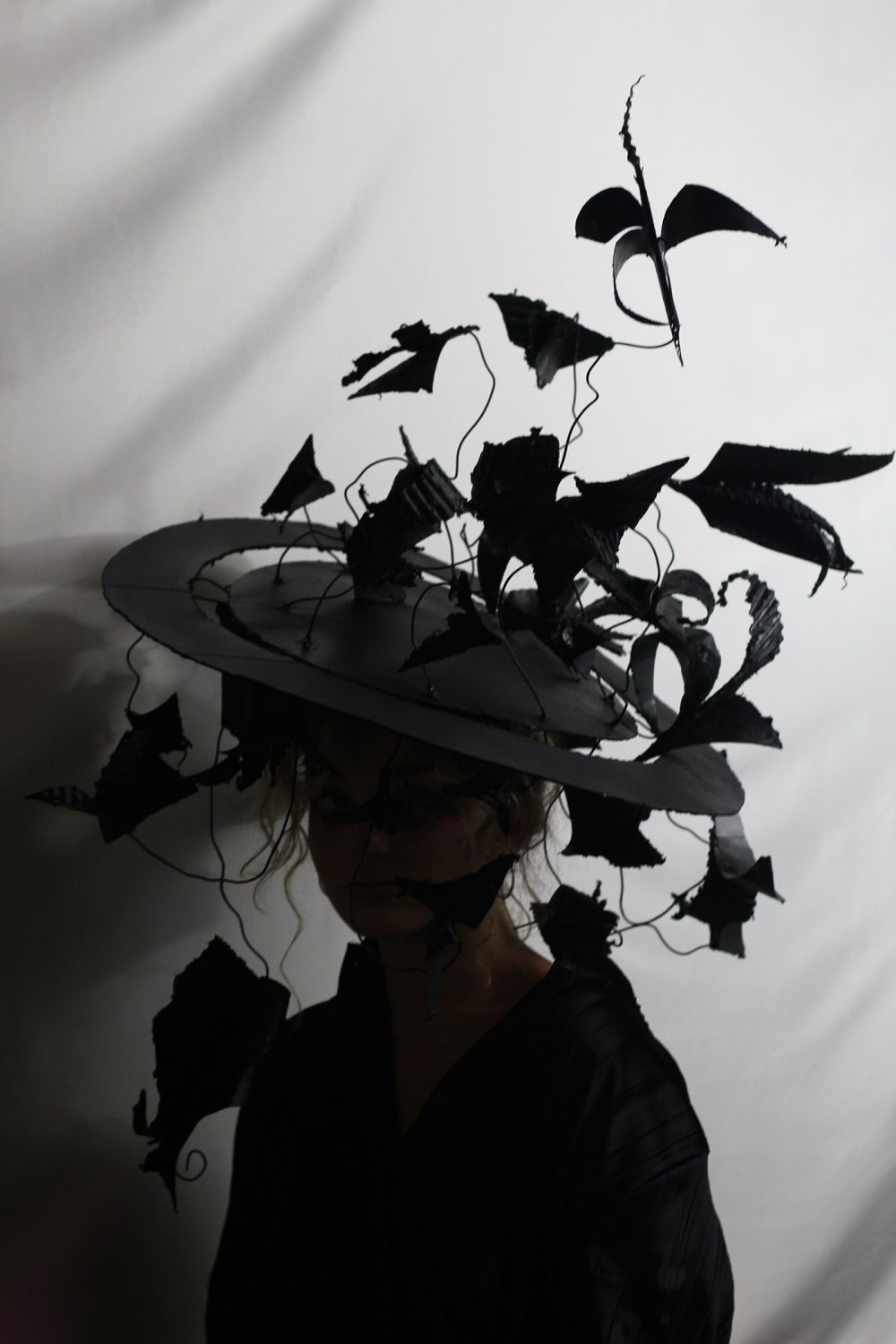 A woman wearing a black hat with a veil of leaves and crows and leaves on top