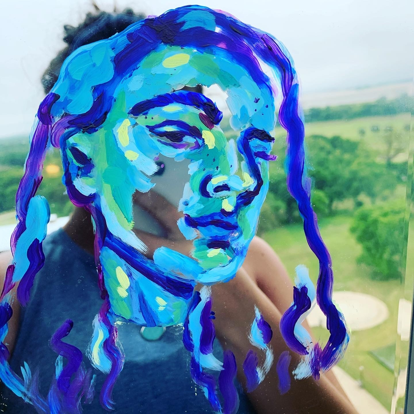 Photograph of a young woman with fields in the background and two-toned blue drawing with a slightly different look over her face
