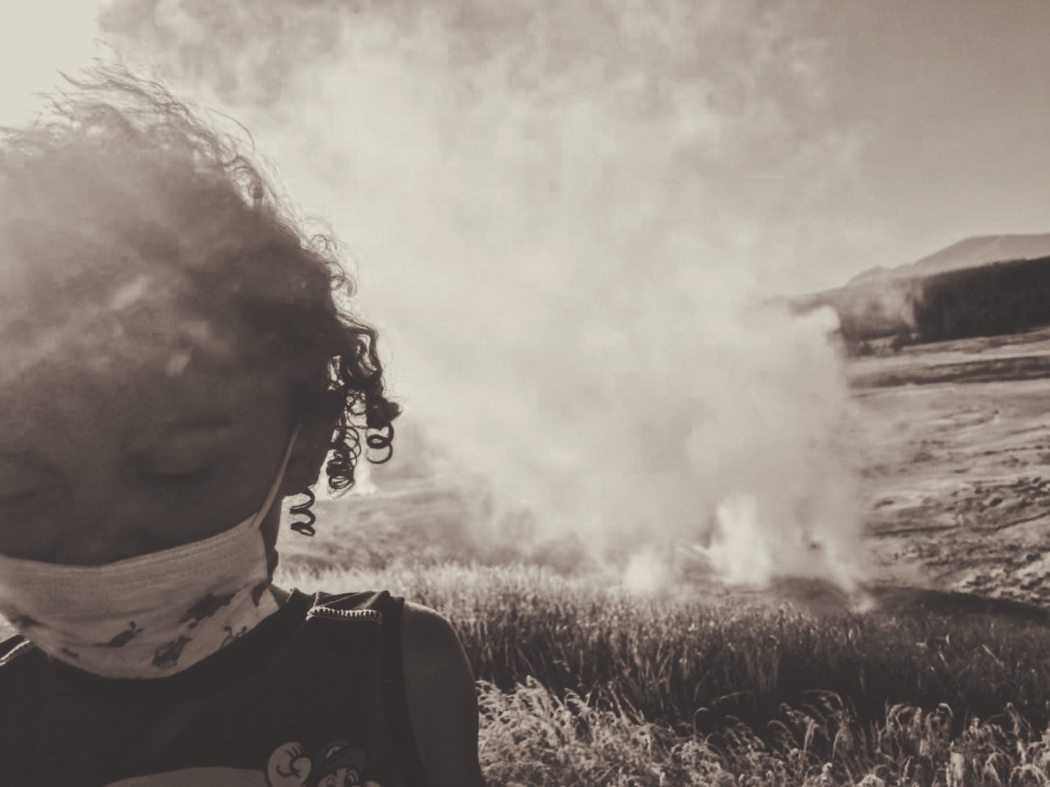 Young girl looking down with a mask on with grass burning in the background