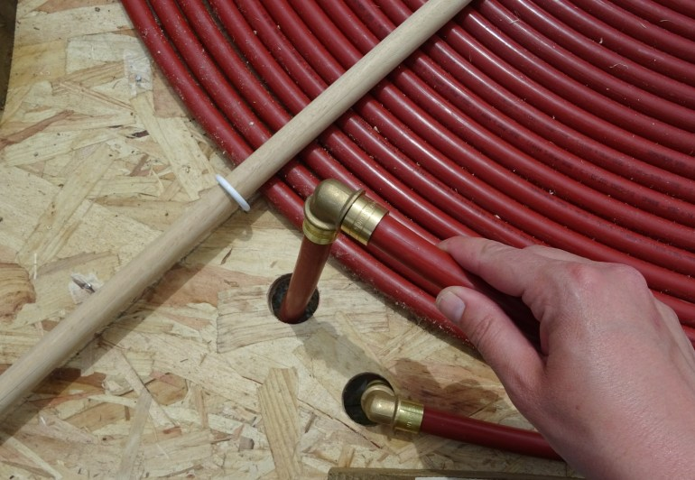 Use elbow connectors to avoid the hose being pinched as it passes through the hole