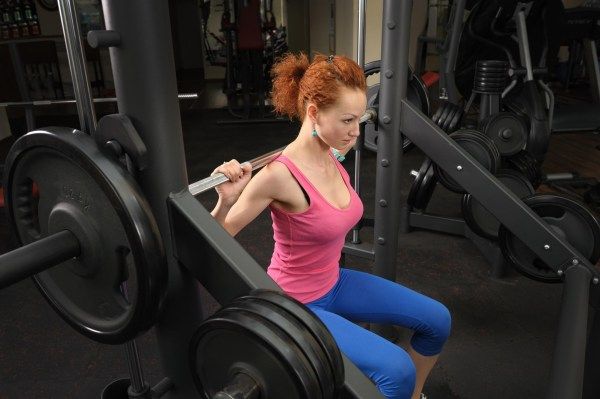 Woman working out on a Smith Cage Machine