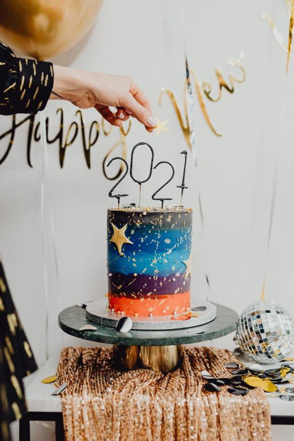 Woman holding a gold star over a cake with 2021 on top