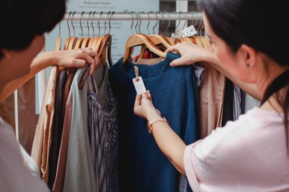 women looking at sweaters on sale