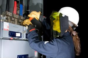 A worker wears face and hand protection while working with electrical current.