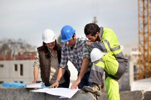 Three workers examine a building plan.